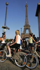 Riders used new bicycles provided by Paris City Hall around the Eiffel Tower yesterday.