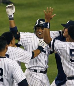 Robinson Cano (center) is greeted by teammates after his single in the 10th inning brought in the winning run.