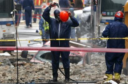 A worker wearing a hazardous-materials suit hosed himself off yesterday at the site of a steam pipe explosion in New York City. Workers were cleaning asbestos-tainted debris.
