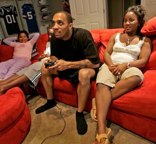 Surrounded by his family, Patriots wide receiver Reche Caldwell, a loyal member of Madden Nation, indulges his favorite pastime.