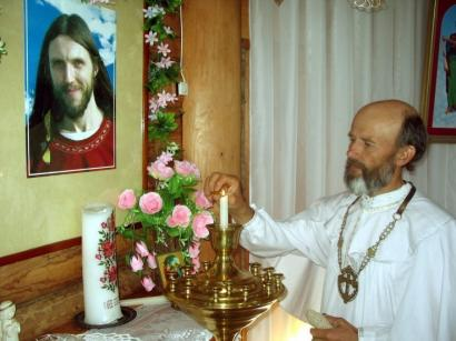 Priest Sergei Chevalkov lit a candle before a photo of Sergei Torop in Abode of Dawn in the Siberian region in Russia.