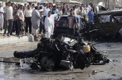 Residents surrounded the wreckage of a tow truck used in a suicide attack in Hillah, Iraq. Sixty-nine people were wounded.