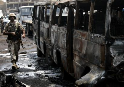An Iraqi soldier walked past the wreckage of a minibus that exploded yesterday in the Tayaran Square area of central Baghdad, killing at least six people and wounding 31.