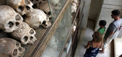 Tourists viewed a memorial yesterday filled with more than 8,000 skulls of victims of the Khmer Rouge on display at Choeung Ek, a 'Killing Fields' site in Cambodia.