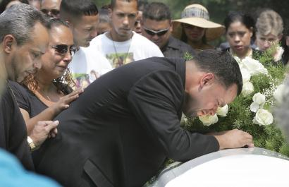 Dennis Burgos cried over the casket of one his children yesterday. His son and daughter were buried at St. Michael's Cemetery in Roslindale. Yasmine and Dennis Jr. were found dead in their Roslindale home July 29. Their mother, Angela Vasquez, has been charged with murder.