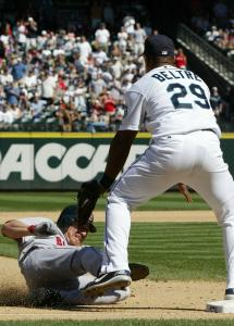 J.D. Drew slides under the Mariners' Adrian Beltre on his way to a triple in the seventh inning.