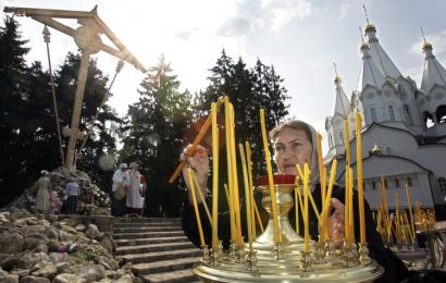A woman lit a candle yesterday near a giant wooden cross commemorating the victims of the political purges of Josef Stalin. The cross was placed on the 70th anniversary of the beginning of mass executions at Butovo, outside Moscow. At least 20,000 people were killed there by Stalin's secret police.
