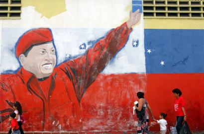 A mural in support of president Hugo Chávez of Venezuela can be seen outside a factory in Caracas. Economic strategists say the country is learning from failed economic models.