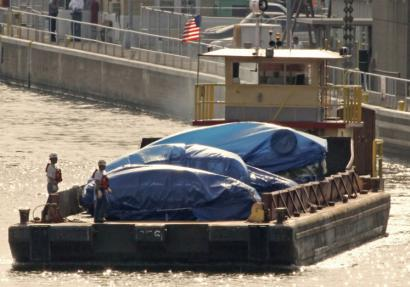 Tarp-covered vehicles were transported by barge from the Interstate 35 West bridge collapse site in Minneapolis.