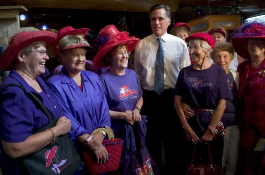 Republican presidential candidate Mitt Romney posed for a photo with the Red Hat Divas of Hampton during a campaign stop at the Camp David restaurant in Iowa Falls, Iowa.