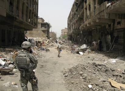 A US soldier stood guard amid debris in Baghdad's central Karrada district yesterday. A car bomb attack more than two weeks ago killed 25 people there and left more than 100 families homeless.