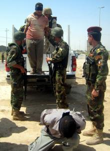 Iraqi soldiers guarded blindfolded suspects yesterday in the restive city of Baqubah. Coalition forces staged simultaneous raids across the country with Operation Phantom Strike.