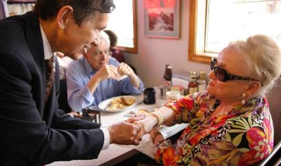 Democratic presidential hopeful Dennis J. Kucinich greeted diners Lilo Levey of Nashua and her husband, Louis, yesterday at Red Arrow Diner in Manchester, N.H. At another stop, he told clients of the Families in Transition program in Manchester that he understands their struggle. Kucinich moved 21 times -- sometimes into the family car -- by the time he was 17.