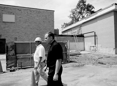 The Rev. James Flavin, who ran St. Edward's School, and Suffolk Construction site manager Kevin Lahti walked the grounds of what will become Trinity Catholic Academy. Three Brockton elementary schools have been regionalized into the new academy.