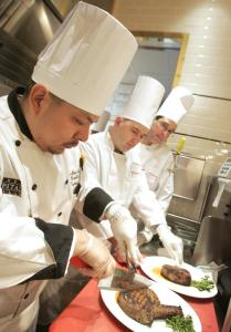 A Capital Grille chef (left) instructs broilers at the restaurant's Burlington location earlier this year. The restaurant's owner is set to be acquired in a $1.19 billion deal.