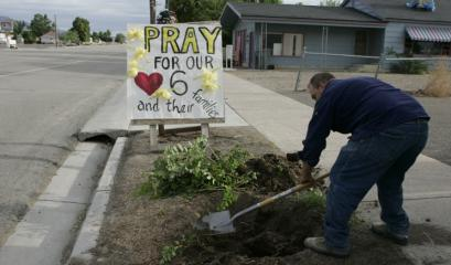 Ryan Wilson, 27, does some landscaping in front of a sign supporting the trapped miners yesterday in Huntington, Utah.