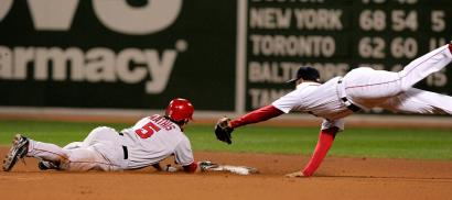Red Sox second baseman Alex Cora's diving tag is too late to prevent Angel Jeff Mathis's double in the fourth inning.