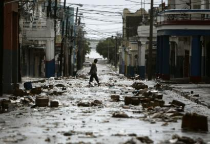 A resident walks through a debris-filled street in Kingston, Jamaica, yesterday. Hurricane Dean brought heavy winds and torrential rains to the island and is expected to hit the Cayman Islands today.