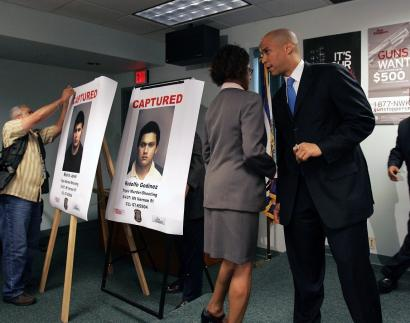 Mayor Cory A. Booker of Newark talked with an aide yesterday, near posters of two of the six suspects in the execution-style shooting in a schoolyard of three college students.