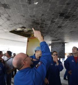 Scott J. Kelly, Space shuttle Endeavour's commander, pointed to the damaged tiles on the underbelly of the spacecraft yesterday at Kennedy Space Center in Cape Canaveral, Fla.