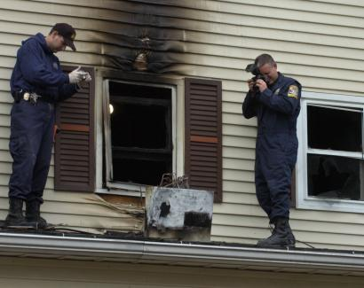 Connecticut State Police Detectives Paul Makuc (left) and Rich Cop photographed an air-conditioning unit on the second floor of a house in Meriden, Conn., after a fire Tuesday morning killed a 2-year-old boy and left two children critically burned.
