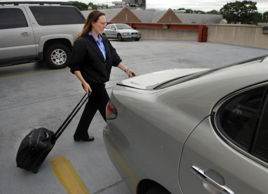 Pulling a briefcase on wheels, Susan Dallabrida walks to her car at a parking garage four blocks from her job at Children's Hospital. She started using such devices three years ago after back surgery and is on her fourth one.