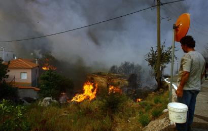 Residents tried to extinguish a burning house in the village of Smerna yesterday. Some of the raging fires, spread by dry winds, have been blamed on arsonists. In Areopolis, a town in the southern Peloponnese, a 65-year-old man was arrested and charged with arson and multiple counts of homicide in a fire that killed six people.