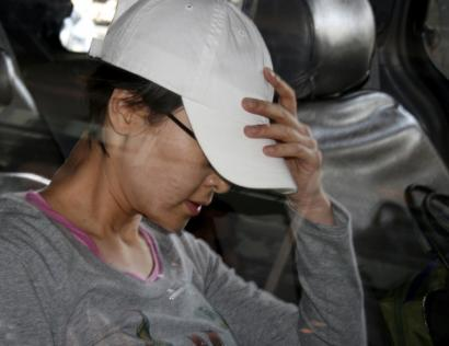 Shin Jeong-ah hid her face from reporters after arriving in New York on July 16. Her whereabouts are unknown.