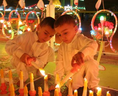 Boys lit candles yesterday for the victims of violence between rival Shi'ite militias in Karbala.