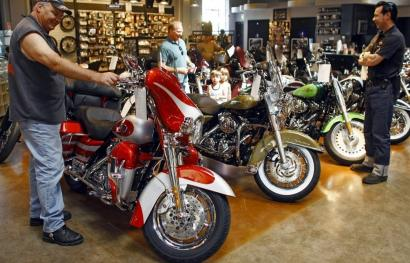 Customers ogle Harley-Davidson motorcycles. Consumer spending rose 0.4 percent in July.