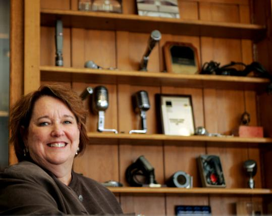 Catherine Shanahan, owner of Shanahan Sound & Electronics, a family-owned business in Lowell, with a display of classic microphones collected over the years.
