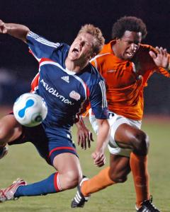 The Revolution's Adam Cristman is fouled by Carolina's David Stokes in the 80th minute.