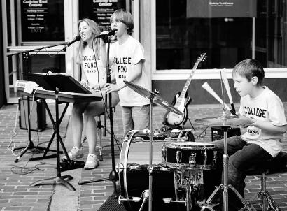 The College Fund Band from Gloucester - Debbie Gantt, and her sons, 12-year-old Jack (standing), and 9-year-old Dan - perform in Harvard Square on a recent Saturday evening.