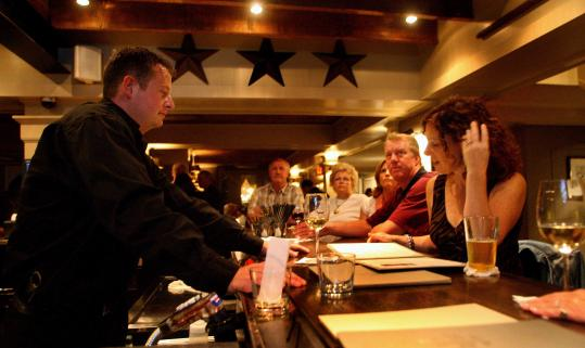 Joe Beal, the bartender at the Scarlet Oak Tavern, takes an order from Diane Flaherty of Norwell. The restaurant is in a 241-year-old Colonial house in Hingham.