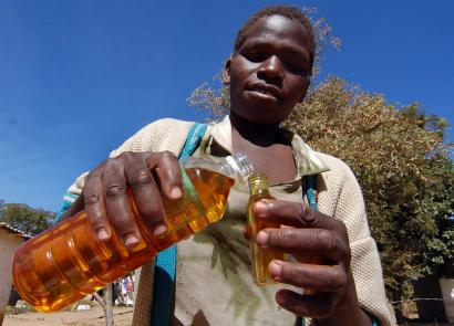 A vendor sold cooking oil, sweet potatoes, and sugar in Harare, Zimbabwe, in July. Cooking oil is often not available in shops, but can easily be found at inflated prices on the black market.