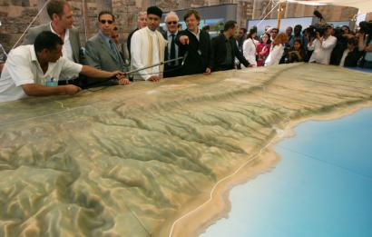 Seif Al-Islam Khadafy's (fourth from left) was briefed next to a model of the proposal. The intention is to make 2,046 square miles of Libya an environmentally sustainable region.