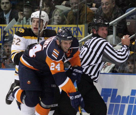 The Islanders' Radek Martinek (24) and the Bruins' Milan Lucic have the referee hemmed in.