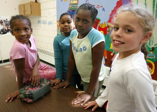 Cambridgeport School students (from left) Raina Williams, 9; Ashley St. Fleur, 9; Perardine Isidore, 9; and Kate Lummis, 8; are taking part in its Science Club for Girls program.