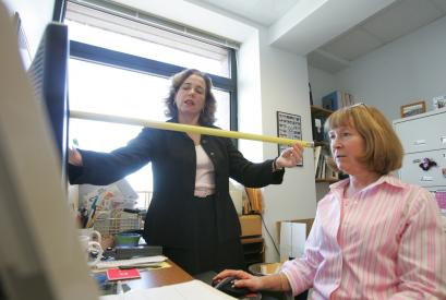 Karen Jacobs, a specialist in ergonomics, takes measurements of a workstation for Joan Gentile, a clinical education assistant. Jacobs seeks to make the workplace less taxing on the workers' bodies.