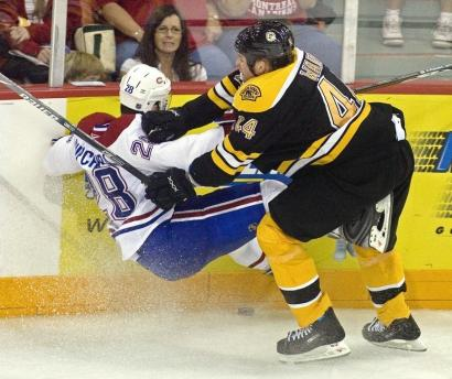 Defenseman Aaron Ward knocks Montreal's Kyle Chipchura off the puck and off his skates.