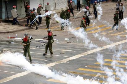 The military released smoke canisters after firing on a crowd of thousands in Rangoon, Burma, during demonstrations yesterday against army rule and economic hardship.