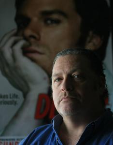 Author Jeff Lindsay, in front of a poster for the Showtime series loosely based on the first of his 'Dexter' novels.