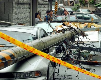 Residents examined cars yesterday that were crushed by fallen electric poles and debris caused by Typhoon Krosa in Taipei.