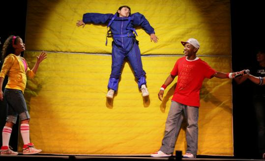 Bernazzani Elementary School pupil Andrew Spada, 10, hangs from a Velcro wall during a hip-hop science education concert focusing on gravity and motion at North Quincy High School.