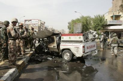 An Iraqi Army vehicle remained in the street after a bombing in Baghdad killed four civilians and two Iraqi soldiers.
