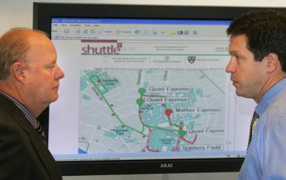 Harvard University transportation services director John Nolan (left) and general manager David Harris look at a map displaying the real-time location of college shuttle buses, available online at shuttle.harvard.edu.