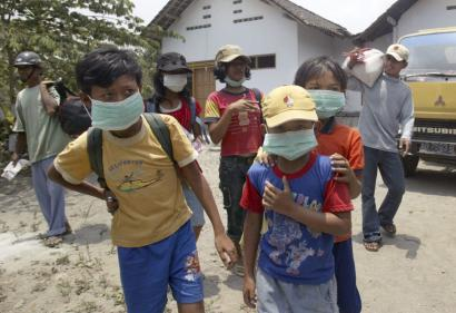 Indonesian youths waited to be evacuated from their village on the slope of Mount Kelud near Blitar, East Java yesterday. Authorities ordered 116,000 people living along the slope to leave.
