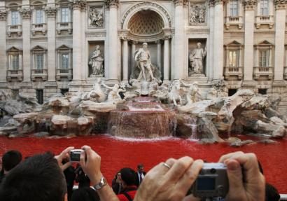 Tourists snapped the red waters flowing Friday in Rome's 17th-century Trevi fountain. After the dye dissipated, artists and critics called the gesture by an unidentified person a brilliant act.