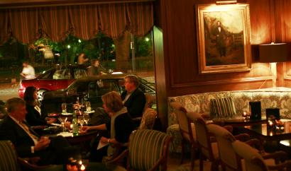 The lounge at the Taj Boston is filled with worn upholstery and dark oil paintings.