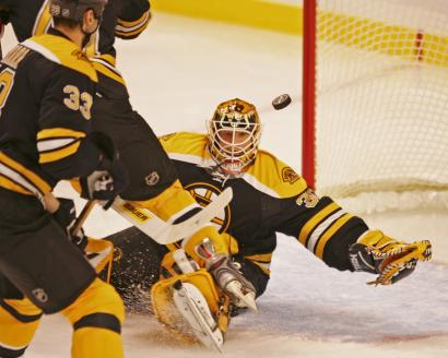 Bruins goalie Tim Thomas keeps the puck in his line of sight while making one of his 26 saves en route to his fourth victory of the season.